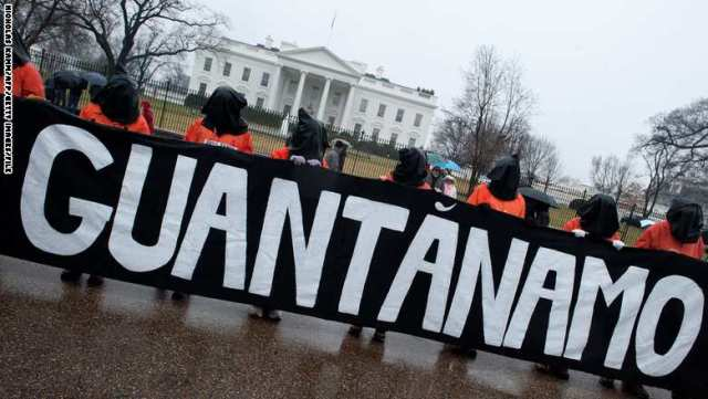 Protestors wear orange detainee jumpsuits and black hoods as they hold a banner calling for the closing of the US detention center at Guantanamo naval base in Cuba in front of the White House in Washington on January 11, 2014 to mark the 12th anniversary of the arrival of the first detainees at the controversial jail. Some 155 people are still held at Guantanamo, more than half of them Yemenis.    AFP PHOTO/Nicholas KAMM        (Photo credit should read NICHOLAS KAMM/AFP/Getty Images)