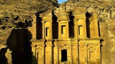 Photo of شخص يقف في مدخل الدير في البتراء يدل على ضخامة المبنى- الأردن