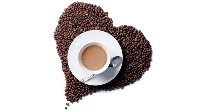 A cup of coffee on a heart shape made from coffee beans