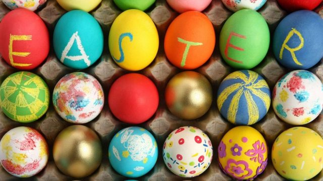 A photograph showing rows of painted eggs in an eggbox, with the uppermost row having the word EASTER chalked on them