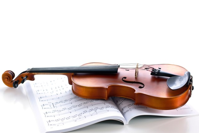 A photograph of a violin resting on a book of sheet music