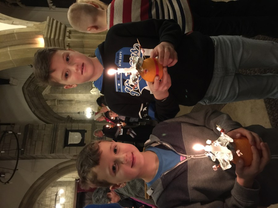 A photograph of two boys holding oranges with candles in them at a previous Christingle service.