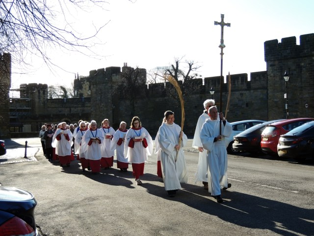 A procession of servers and choristers bearing palms
