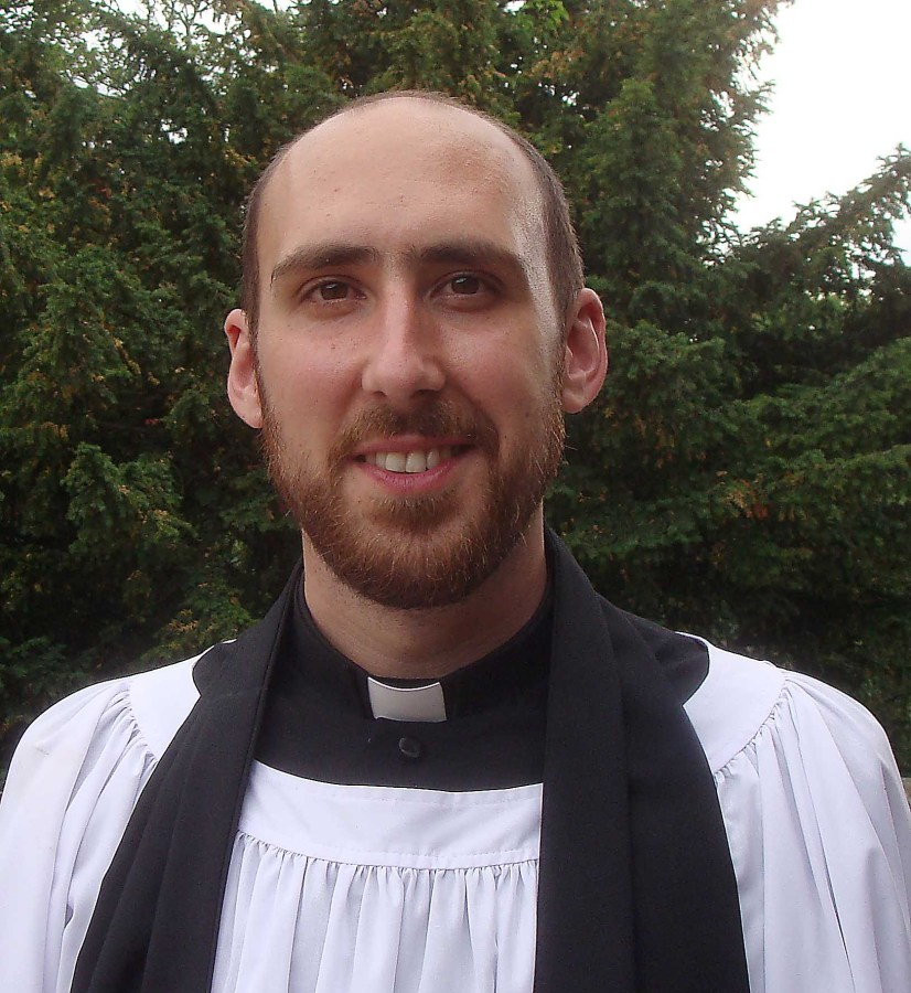 A photograph of a bearded young man in a surplice, black stole and clerical shirt