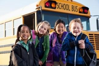 Multi-ethnic children standing in front of school bus.