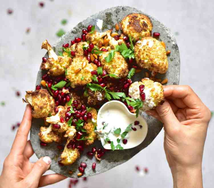 vegetarian baked tahini cauliflower wings with pomegranate and pine nuts.