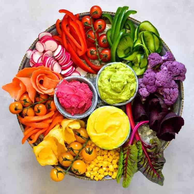 rainbow vegetable platter with hummus three ways. Beetroot hummus, Avocado hummus and Turmeric hummus