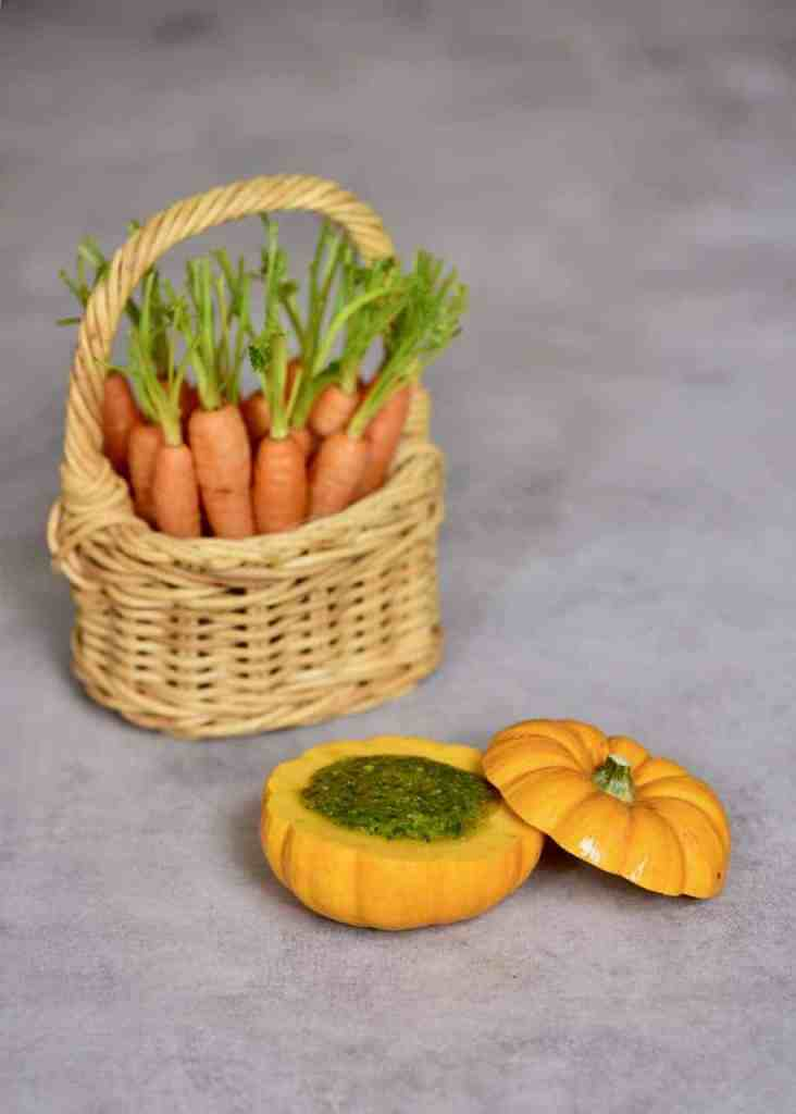 carrots in a basket next to mini pumpkin with homemade carrot pesto in