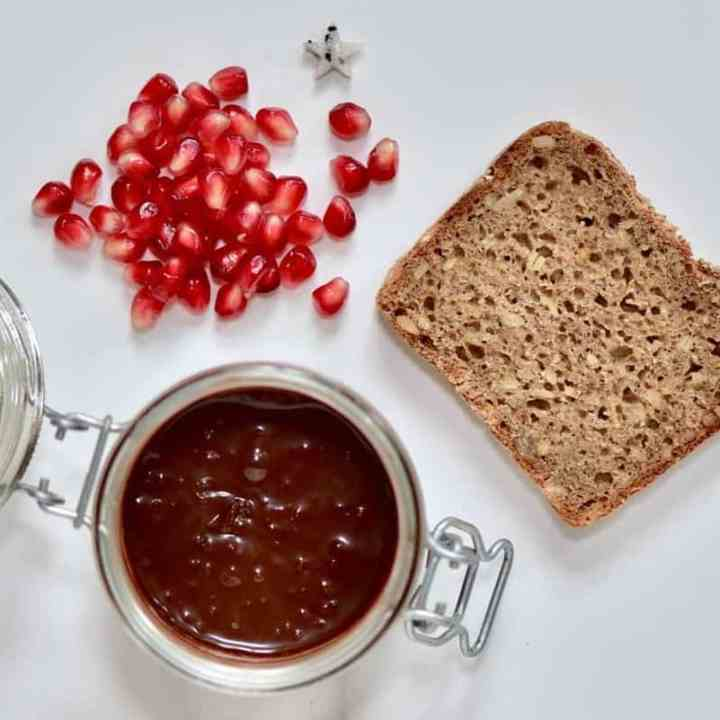 ingredients for homemade healthy christmas toast with healthy vegan nutella spread and pomegranate seeds