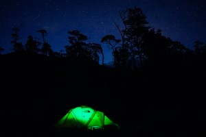 A glowing green The North Face VE 25 stands out among a starry sky in Patagonia..
