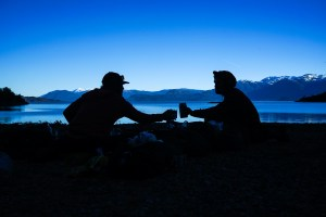 Two silhouettes clink beverages in the early morning in view of the Andes Mountains.