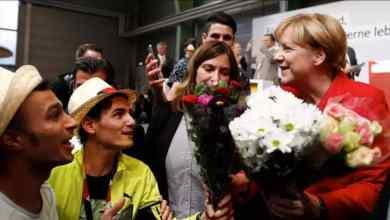 لاجئون سوريون يقدمون الأزهار للمستشارة الألمانية أنغيلا ميركل في شفيرين في شمال ألمانيا في 19 أيلول/سبتمبر 2017. © أ ف ب / أرشيف
