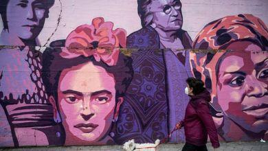 امرأة تمشي قرب الجدارية