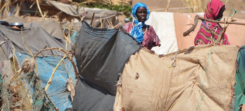 OCHA/Amy Martin نساء نازحات من منطقة جبل مرة في دارفور يقفن بجوار مأواهن المؤقت في طويلة، شمال دارفور.