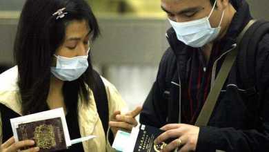 إمرأة وزوجها يرتديان كمامة في هونغ كونغ AFP