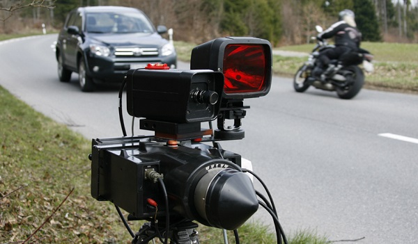 A car and a motorbike pass next to a radar device during a speed check on the Route du Mollendruz in Mont-la-Ville, 60 kilometres (37 miles) west of Geneva April 7, 2009. REUTERS/Denis Balibouse(SWITZERLAND POLITICS CRIME LAW) - RTXDQQ7