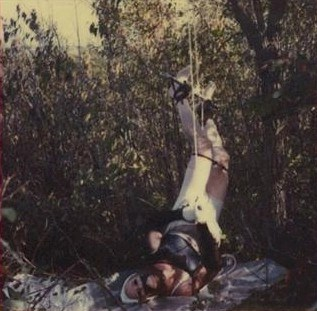 Photo of BTK killer (Dennis Rader) wearing victim's clothes, bound, and hanging from a tree