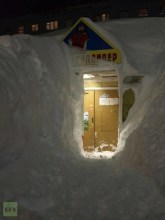 Tunnel dug through snow to a doorway
