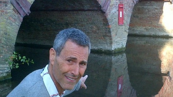 Uri Geller points to a mysterious red letterbox placed on a pillar of a bridge crossing the River Thames