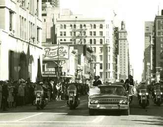 President's car on Main Street, approaching Houston Street, about to enter Dealey Plaza.