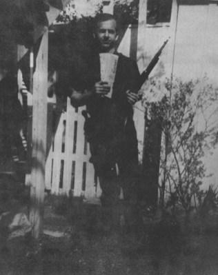 Lee Harvey Oswald poses with rifle