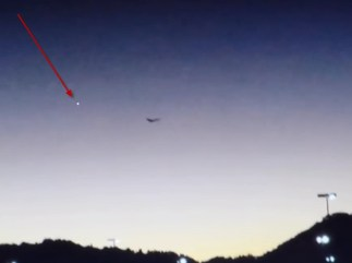 The first burst of white light seen in the sky to the left of the butterfly-ufo