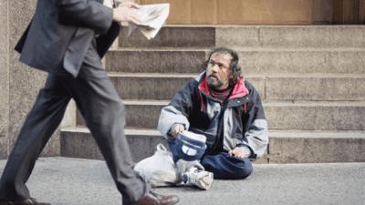 Homeless man watches business man pass by