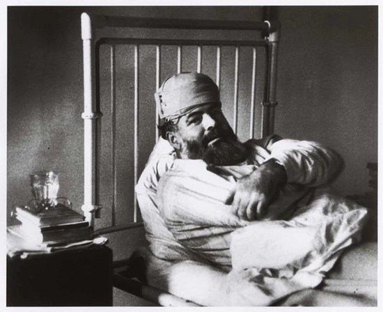 Ernest Hemingway in a hospital bed after one of his many accidents