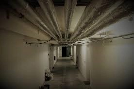 Long hallway tunnel with pipes