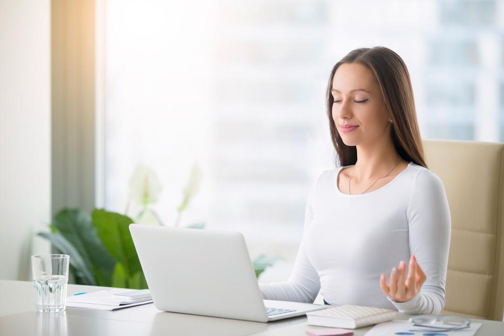 bien-être au travail, jeune femme à son bureau en position de détente
