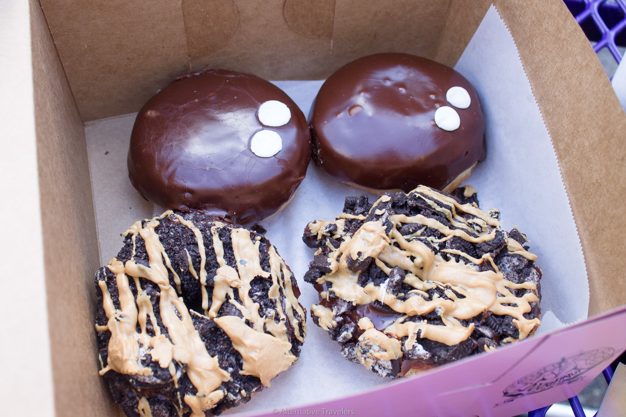 box of chocolate iced and topped vegan donuts at Voodoo Donuts in Portland.