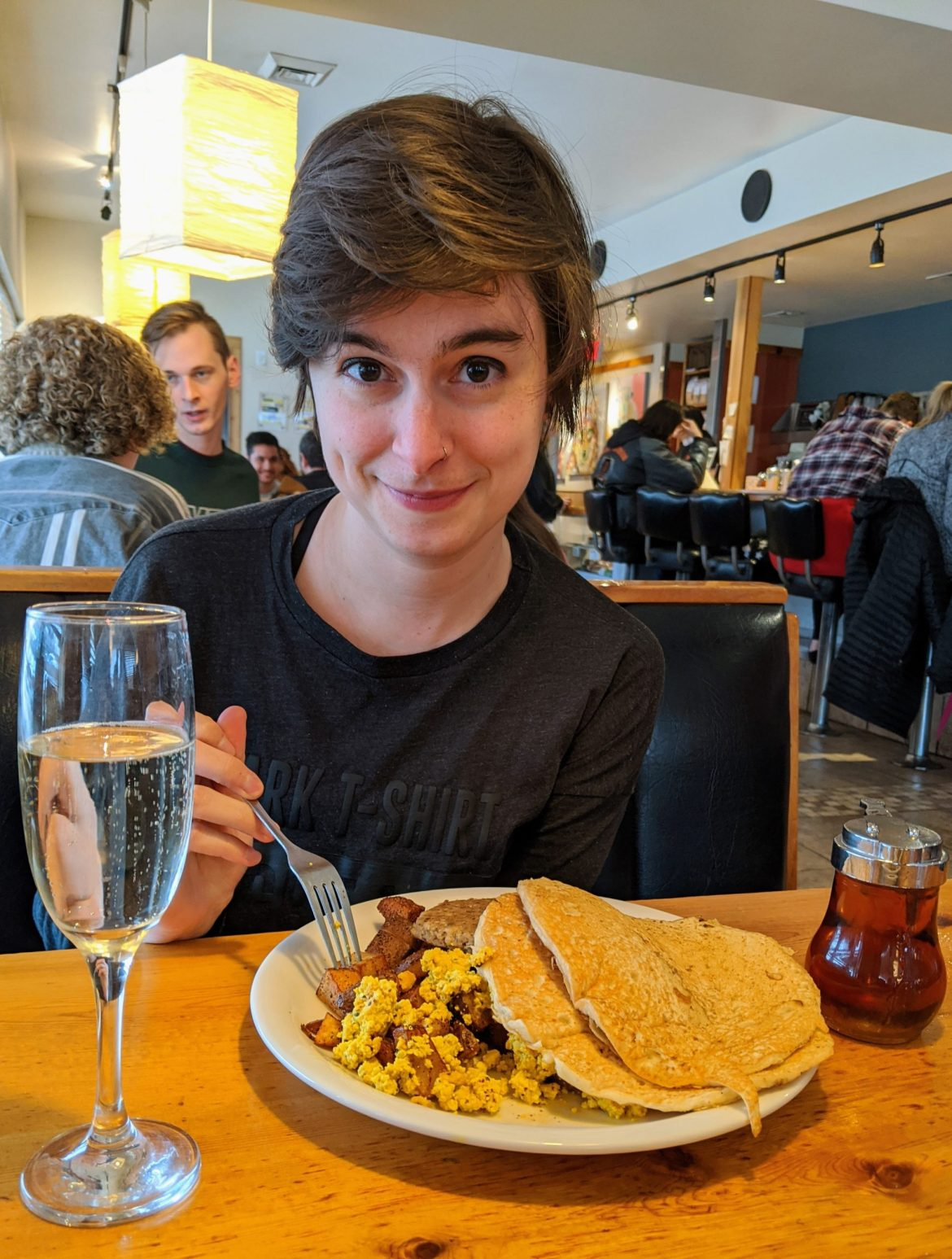 woman smiling at the camera with a breakfast plate and champagne
