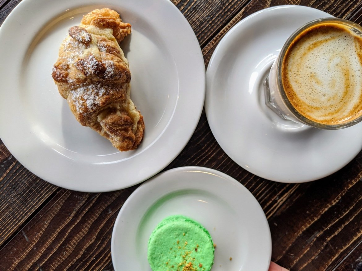 overhead view of croissant, macaroon, and cortado