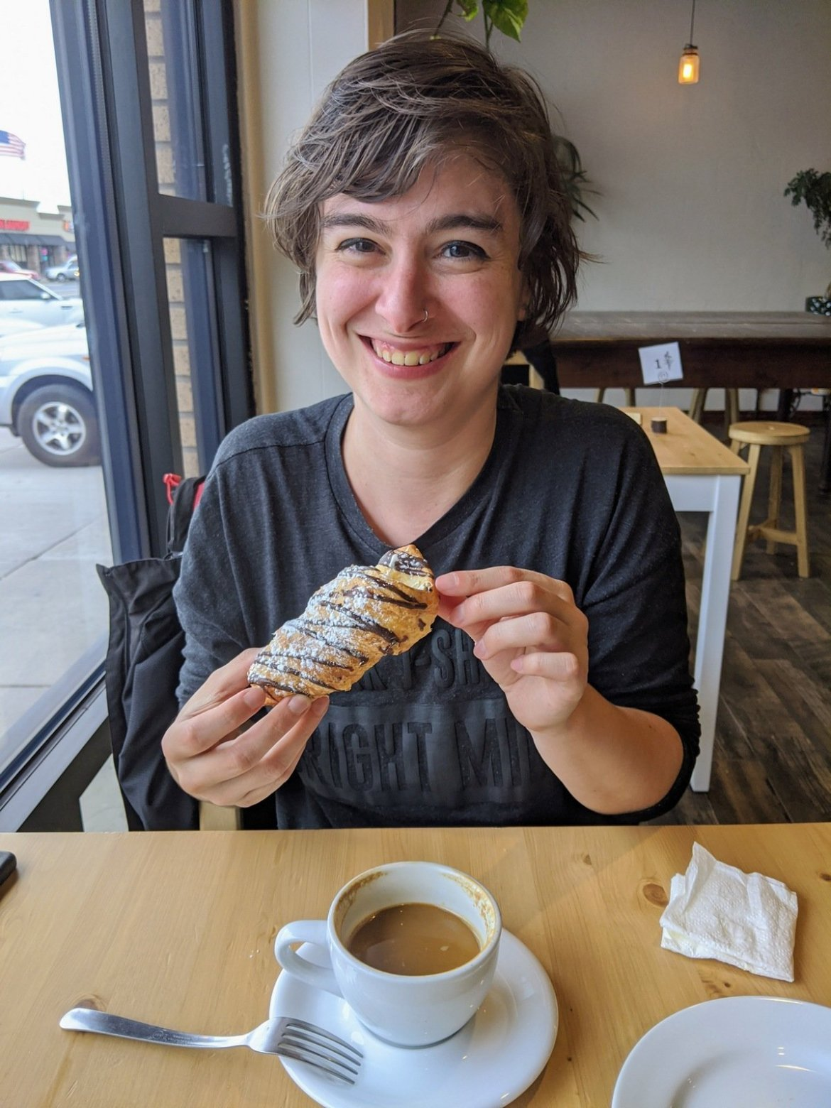 woman holding vegan pastry and coffee cup in front