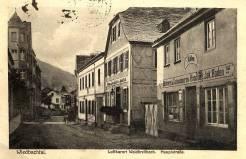 """Diese Straßenszene vermittelt ein Bild, in welcher Weise die Wirts- und Gasthäuser und auch die """"Colonialwarenhändler"""" die Dorfstraße beherrschten. Der Abschnitt von der Marien-Apotheke bis zur Alten Schule am alten Kreuz war seit 1895 mit einer Pflasterung befestigt. Das erste Haus rechts ist die """"Bäckerei und Colonialwarenhandlung Jacob Boden"""" mit der Telefonnummer 12. Es schließt sich an """"Gasthaus zur Sonne - Bäckerei von Johann Kröll"""", erste nachweisliche Schankerlaubnis von 1854. Im nachfolgenden Haus """"Scheid"""" (Post-Scheid) befinden sich die Diensträume der Post. (Richard Schicker 1997)"""