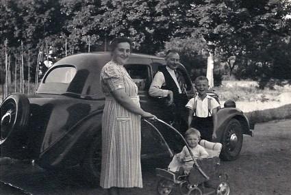 """Familie Gretchen und Johann Reuschenbach mit den Söhnen Hans und Jo im Kinderwagen um 1939/40 vor ihrem Ford """"Eifel"""""""