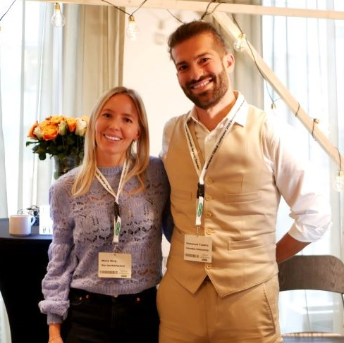 Marie Berg og Emmanouil Tsamis står ved siden av hverandre og smiler mot kamera, de har specsavers konferanse navneskilt rundt halsen