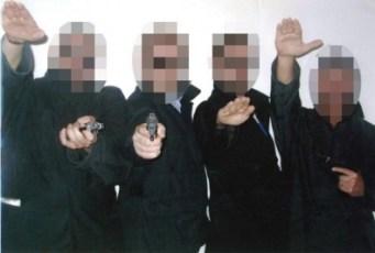 Neonazis aus Varese posen mit zum Gruß erhobenem Arm und halbautomatischen Pistolen.