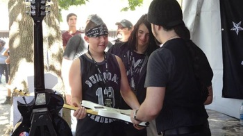 Fan having a guitar autographed at the Crazy Dave's Music Experience