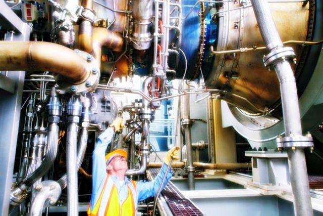 পাওয়ার ইঞ্জিনিয়ারিং কাজে ব্যস্ত এক ইঞ্জিনিয়ার অতিকায় গ্যাস টারবাইন পর্যবেক্ষণ করছেন যা জেনারেটরের বিদ্যুৎ উৎপাদনে প্রধান ভূমিকা রাখে
