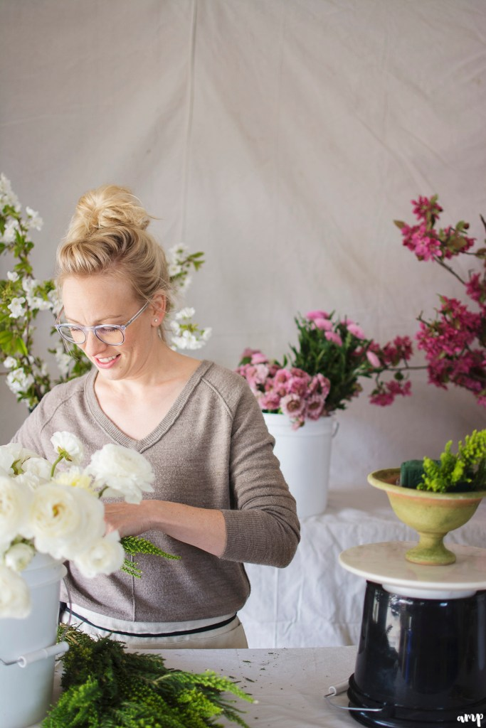 Kelly Mendenhall of 3 Leaf Floral arranging a centerpiece