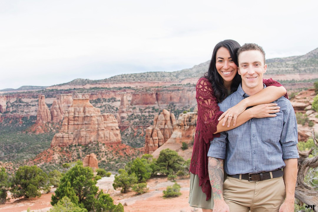 Engaged couple standing before a canyon with her arms around his shoulders