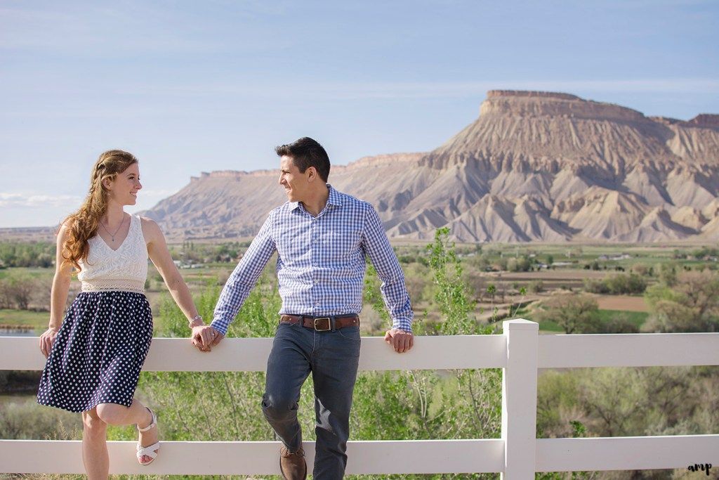 Couple leaning on fence overlooking Mt. Garfield