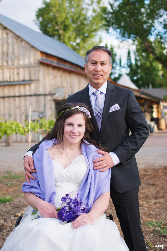 Newlywed couple with bride in wheel chair outside a winery