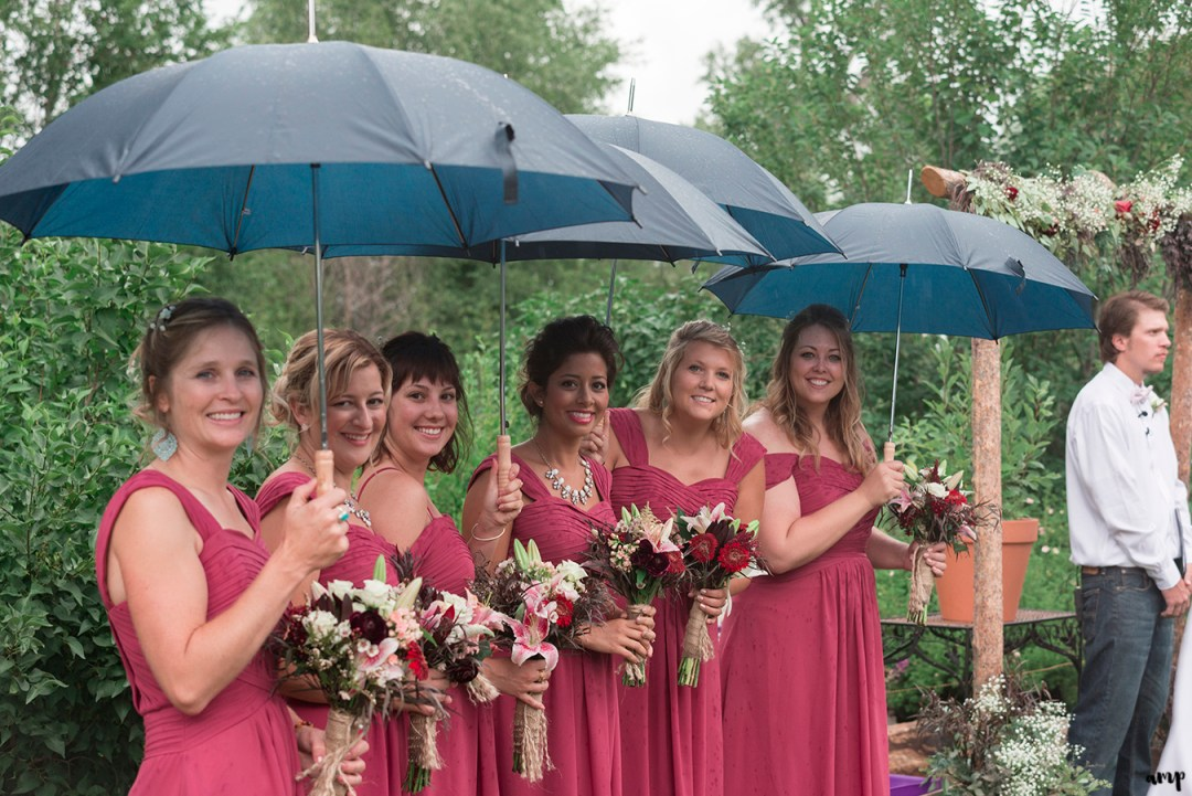 Bridesmaids under umbrellas at the Gunnison wedding along Ohio Creek