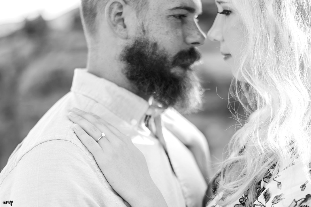 Black and white photo focused on the engagement ring as couple cuddles