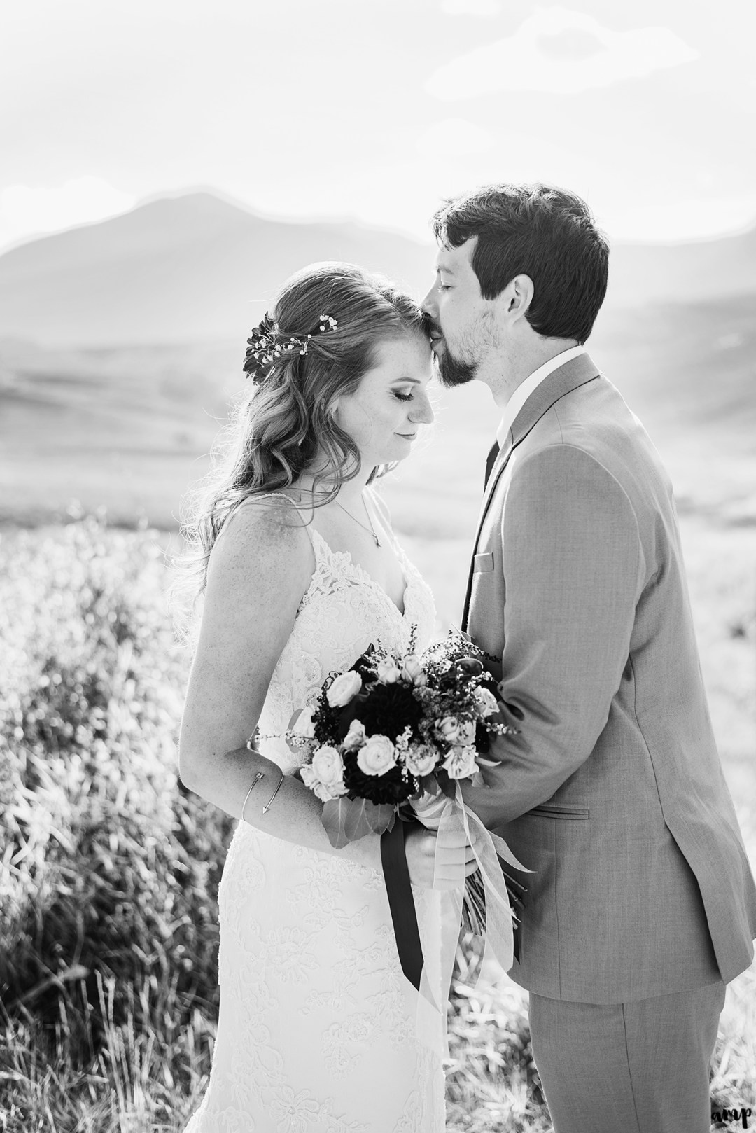 Black and white image of groom kissing his bride's forehead