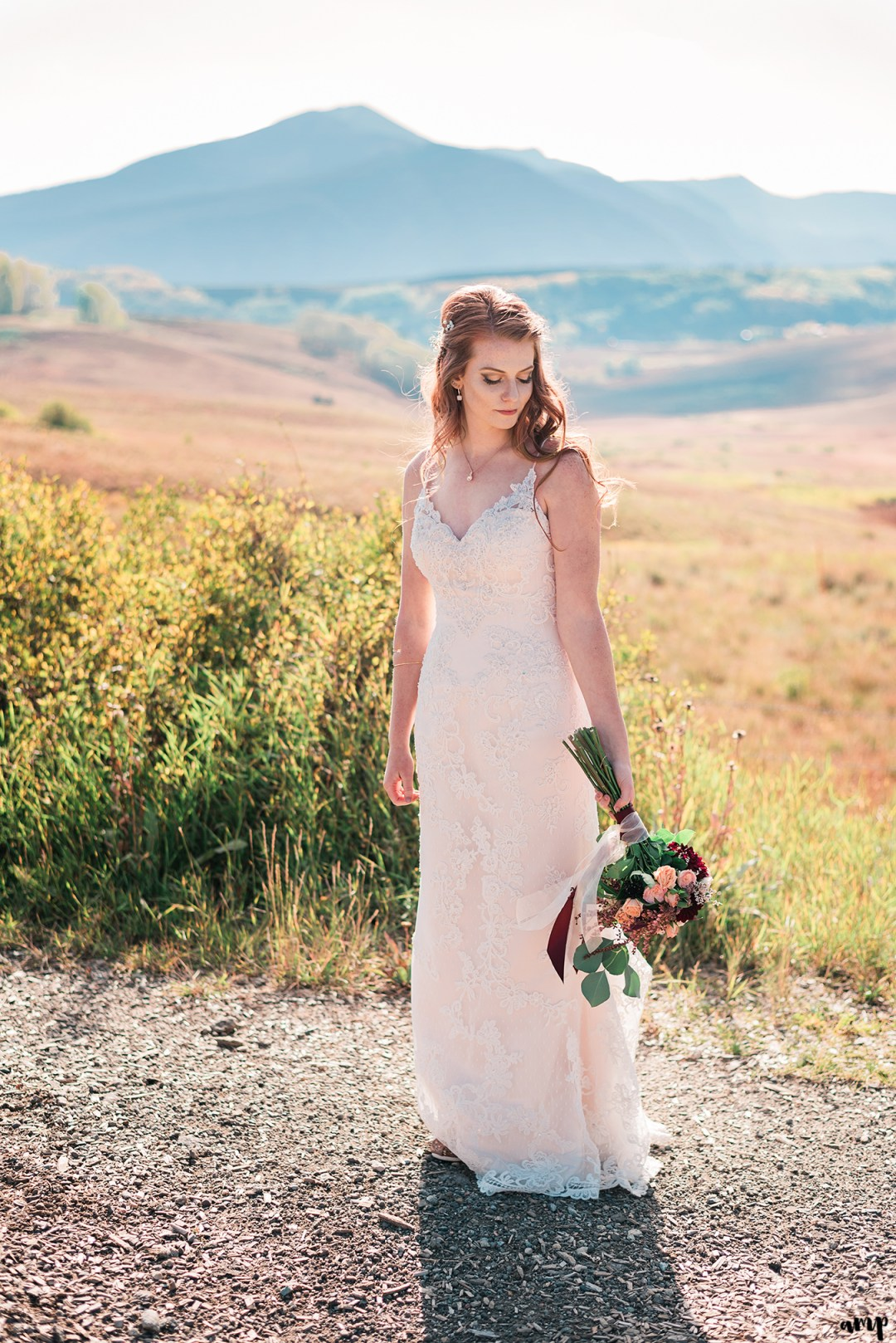 Bride gazing at her bouquet among the fall colors with mountains in the background