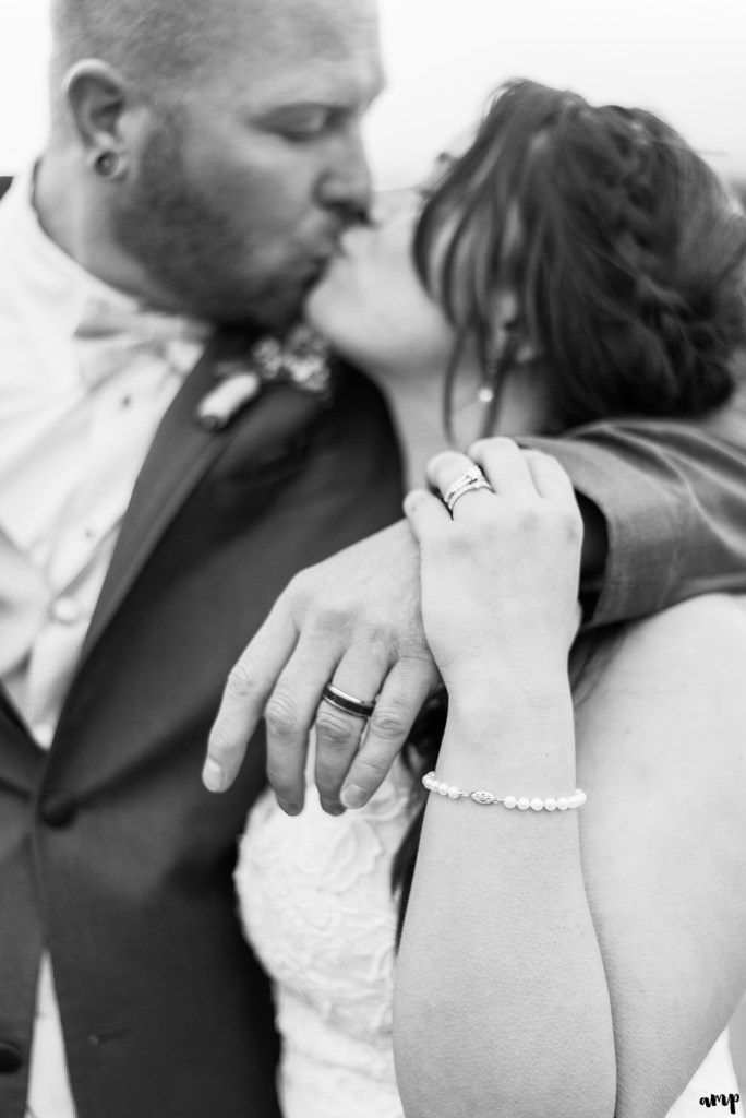 Black and white photo of bride and groom kissing, focused on the rings