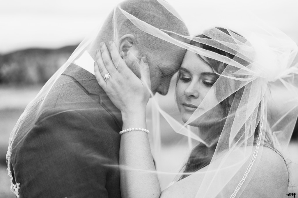 Bride and groom snuggle under her veil